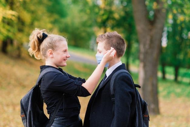 Uczniowie, chłopiec i dziewczynka w maskach medycznych spacerują po parku miejskim.