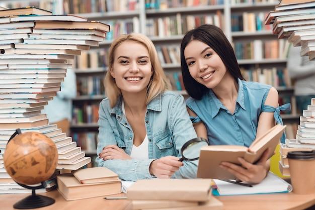 Uczniowie czytają książkę w szkolnej bibliotece.