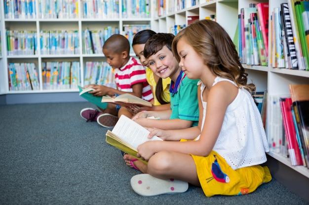 Uczniowie czytający książki siedząc w szkolnej bibliotece