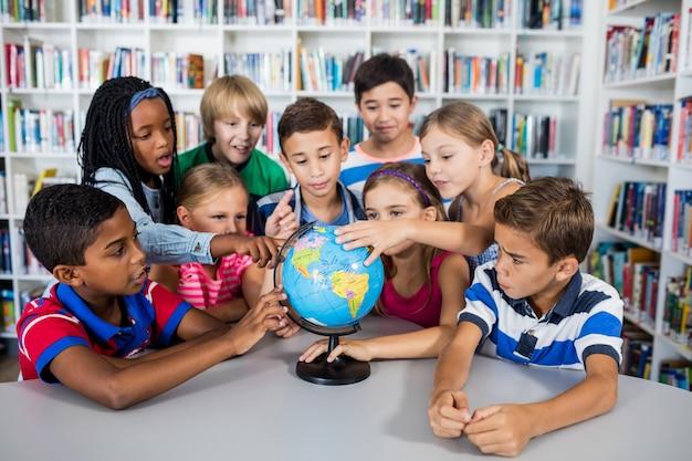 Uczniowie dotykają globu