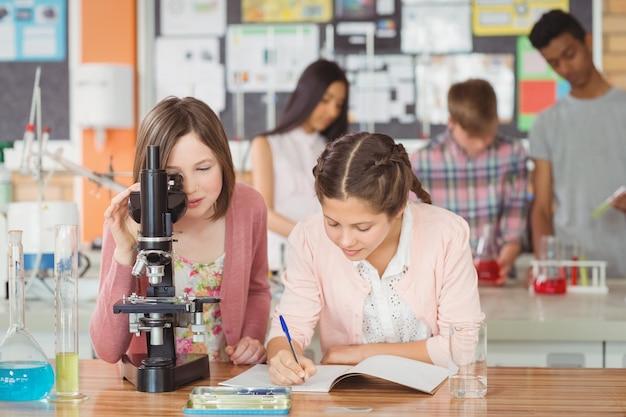 Uczniowie eksperymentujący na mikroskopie w laboratorium w szkole w laboratorium