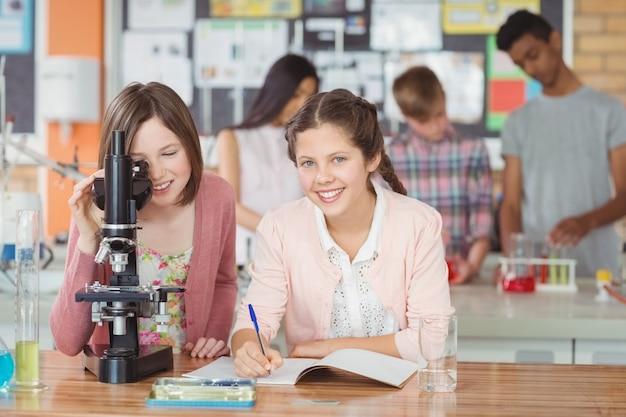 Uczniowie eksperymentujący z mikroskopem w laboratorium w szkole
