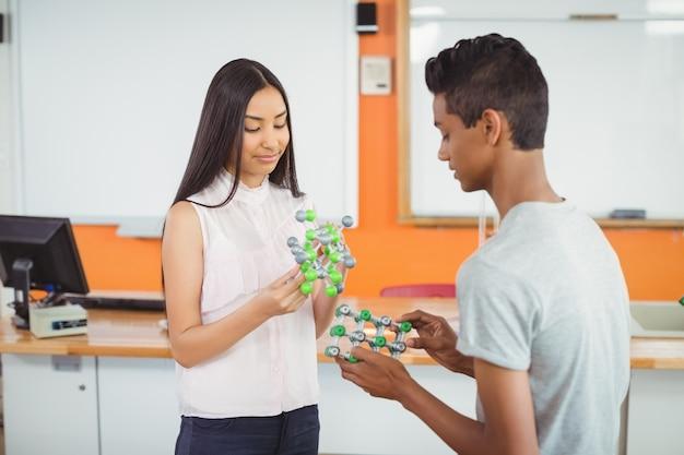 Uczniowie eksperymentujący z modelem cząsteczki w laboratorium