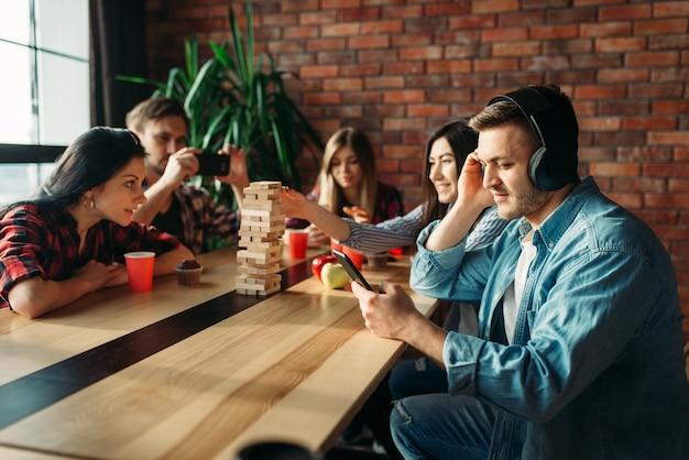 Uczniowie grający jengę przy stole w kawiarni
