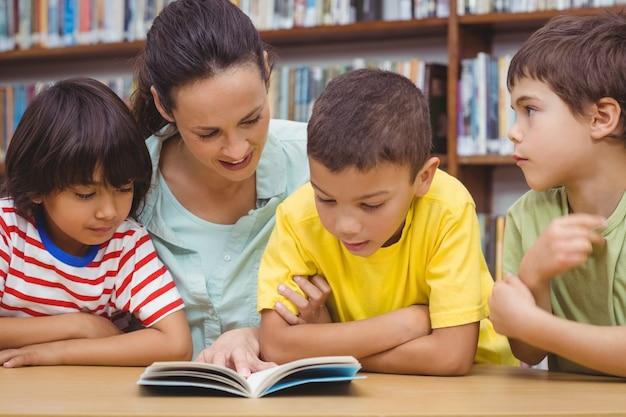 Uczniowie i nauczyciel czytanie książki w bibliotece
