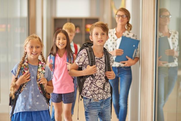 Uczniowie i nauczyciel idący przez korytarz