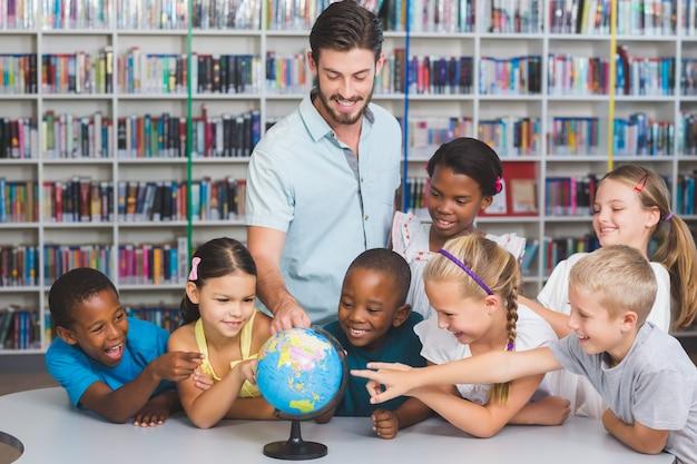 Uczniowie i nauczyciel patrząc na świecie w bibliotece