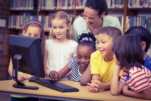 Uczniowie i nauczyciel w bibliotece za pomocą komputera