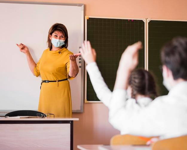 Uczniowie i nauczyciel z maską w klasie
