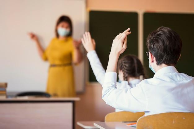 Uczniowie i nauczyciel z maską