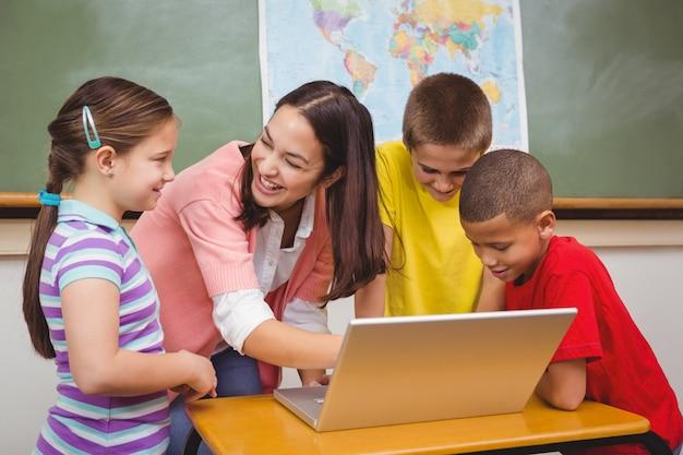Uczniowie i nauczyciel za pomocą laptopa