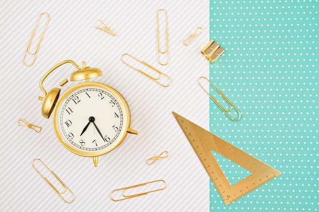 Uczniowie i szkolne złote zapasy z budzikiem. powrót do pomysłu na materiały szkolne i biurowe