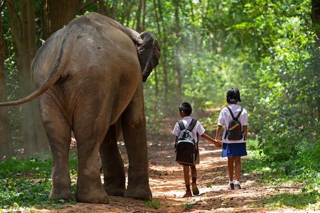 Uczniowie idący do szkoły z dużym słoniem