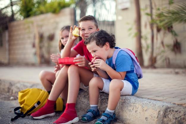 Uczniowie jedzący przekąskę na świeżym powietrzu. koncepcja dzieci, edukacji i odżywiania