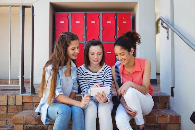 Uczniowie korzystający z telefonu komórkowego na klatce schodowej