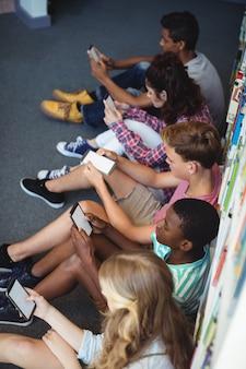 Uczniowie korzystający z telefonu komórkowego w bibliotece