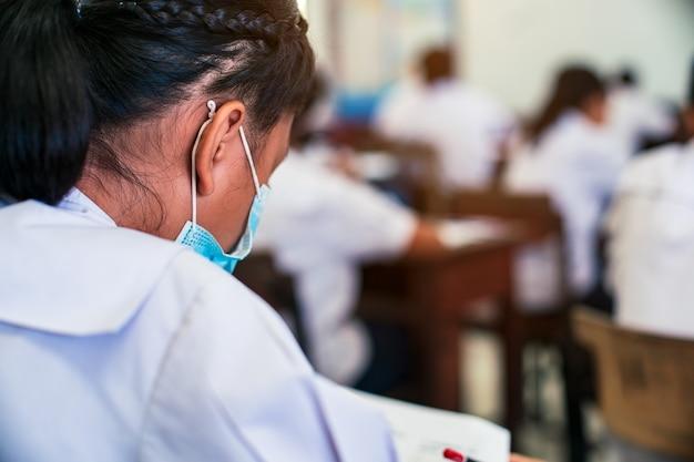 Uczniowie noszący maskę w celu ochrony covid-19 i zdający egzamin w klasie ze stresem.
