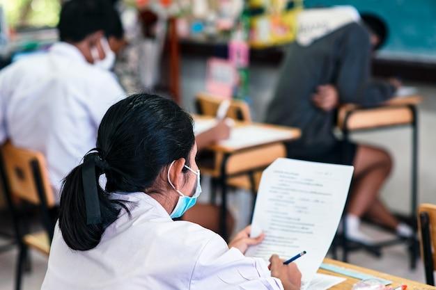 Uczniowie noszący maskę w celu ochrony covid-19 i zdający egzamin w klasie ze stresem