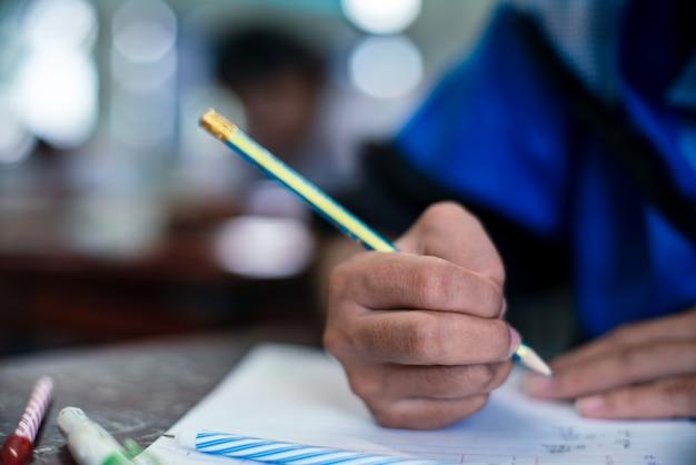 Uczniowie pisząc i czytając arkusze egzaminacyjne odpowiadają na ćwiczenia w klasie szkoły ze stresem