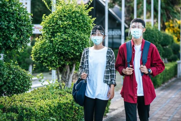 Uczniowie płci męskiej i żeńskiej noszą chłód na twarz i maski spaceruj po chodniku