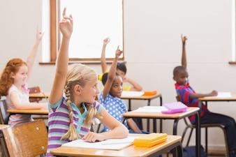 Uczniowie podnoszą ręce podczas lekcji w szkole podstawowej