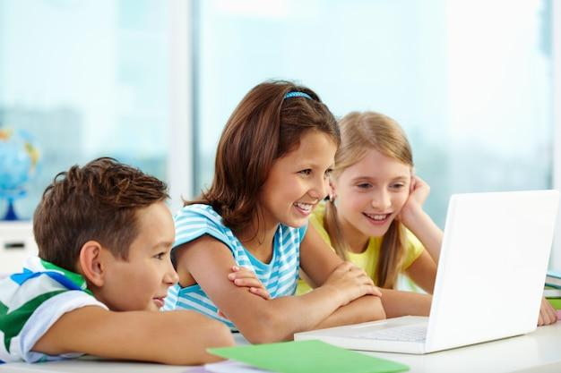 Uczniowie pracują razem na laptopie