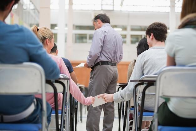 Uczniowie przekazują notatkę za plecami nauczyciela