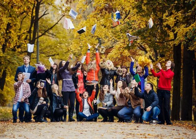 Uczniowie rzucają swoje zeszyty po ukończeniu studiów