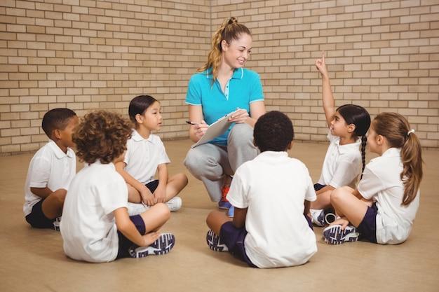 Uczniowie siedzą i słuchają nauczyciela