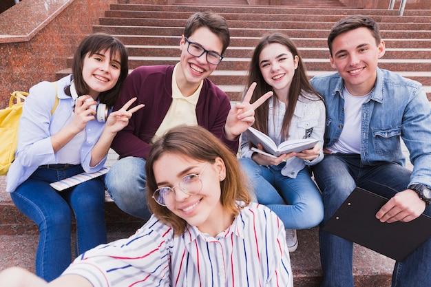 Uczniowie siedzą na schodach i gestykulacji dwa palce patrząc na kamery
