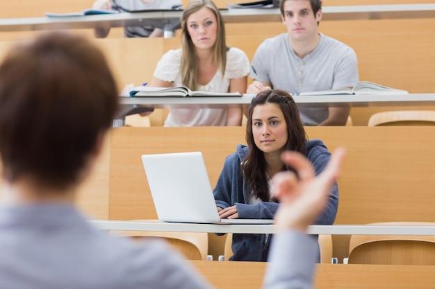 Uczniowie siedzą słuchając nauczyciela
