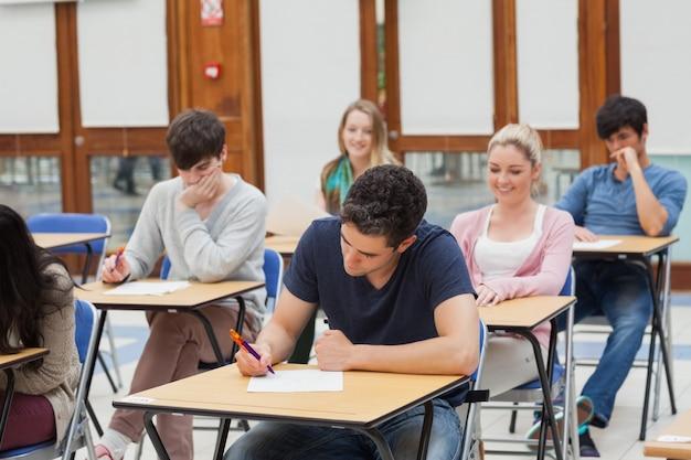Uczniowie siedzący przy pisaniu pokoju egzaminu