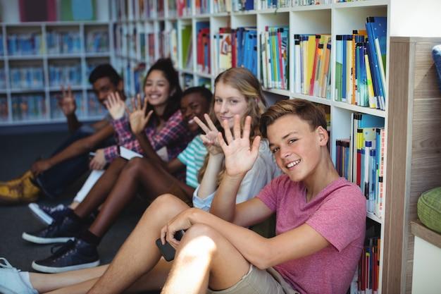 Uczniowie siedzący w bibliotece i machający rękami