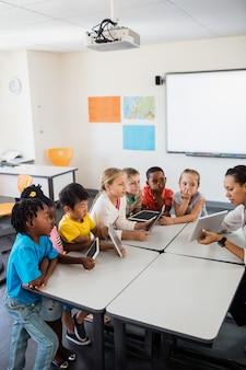 Uczniowie słuchają nauczyciela za pomocą komputera typu tablet