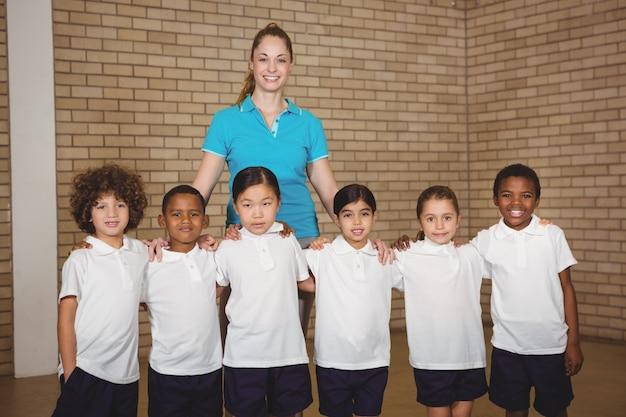 Uczniowie sportowi stoją razem z nauczycielem