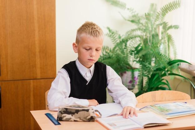 Uczniowie szkół podstawowych piszący w książkach w klasie