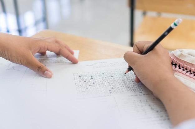 Uczniowie szkoły biorą egzaminy, pisząc egzamin trzymając ołówek na optycznej formie znormalizowanej