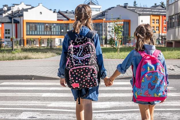 Uczniowie szkoły podstawowej chodzą do szkoły trzymając się za ręce pierwszego dnia szkoły z powrotem do szkoły
