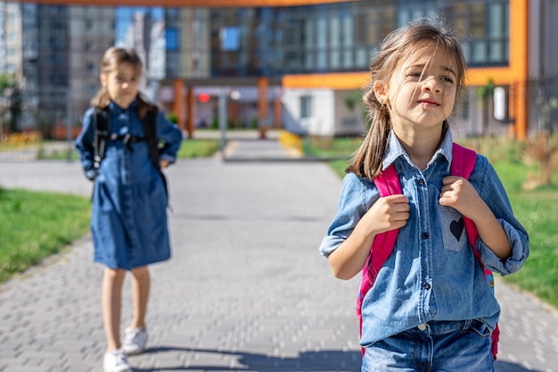 Uczniowie szkoły podstawowej. dziewczyny z plecakami w pobliżu budynku na zewnątrz. początek lekcji. pierwszy dzień jesieni.