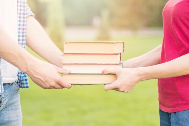 Uczniowie trzyma książki w parku
