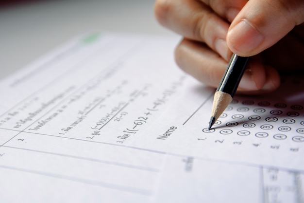 Uczniowie trzymają ołówkiem pisanie wybranym wyborem na arkuszach odpowiedzi i arkuszach pytań matematyki