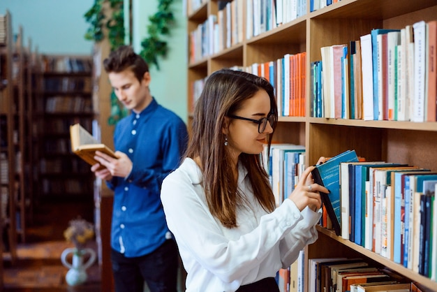 Uczniowie w bibliotece poszukujący materiałów do wykonania projektu grupowego