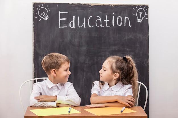 Uczniowie w klasie przy biurku na tle łupka