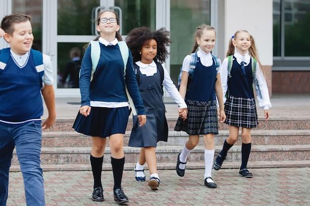 Uczniowie w mundurkach iz plecakami chodzą do szkoły.