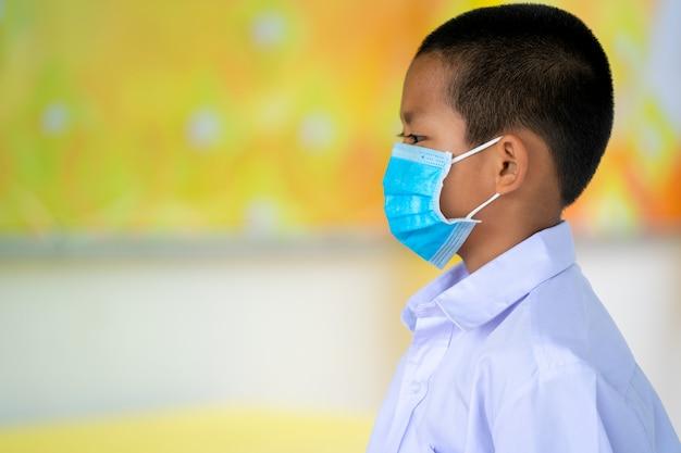 Uczniowie z azji noszą ochronną maskę na twarz dla bezpieczeństwa w szkole podstawowej.