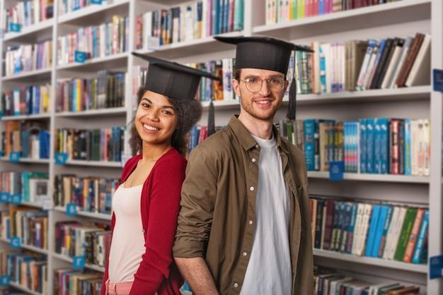 Uczniowie z czapkami stojący w bibliotece