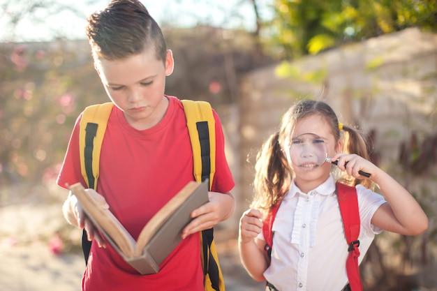 Uczniowie z książką i lupą na zewnątrz. powrót do szkoły. koncepcja dzieci i edukacji