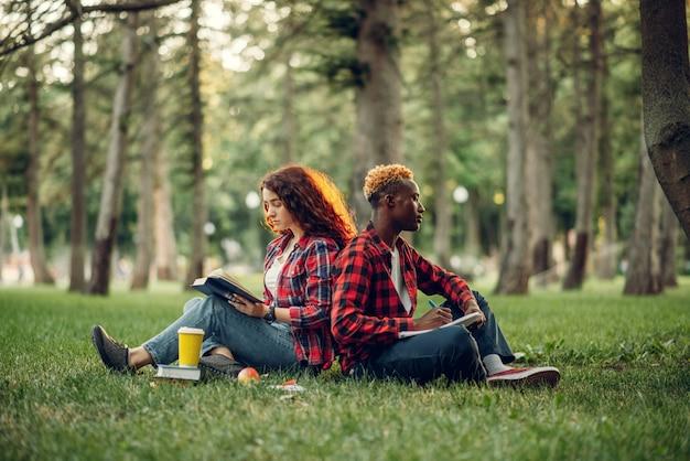 Uczniowie z książką siedzą na trawie plecami do siebie, letni park. nastolatki płci męskiej i żeńskiej uczące się na świeżym powietrzu i jedzące obiad