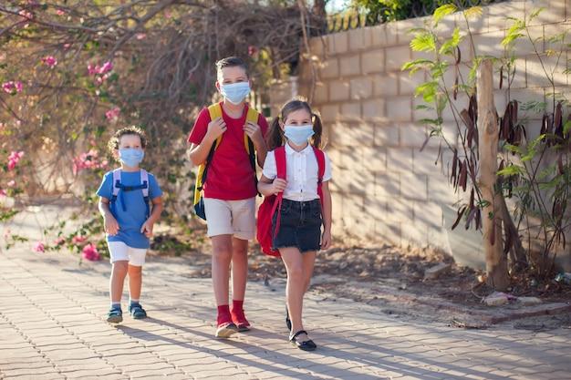 Uczniowie z maskami medycznymi na twarzy i plecakami na świeżym powietrzu. edukacja w okresie koronawirusa. dzieci i opieka zdrowotna. powrót do szkoły.