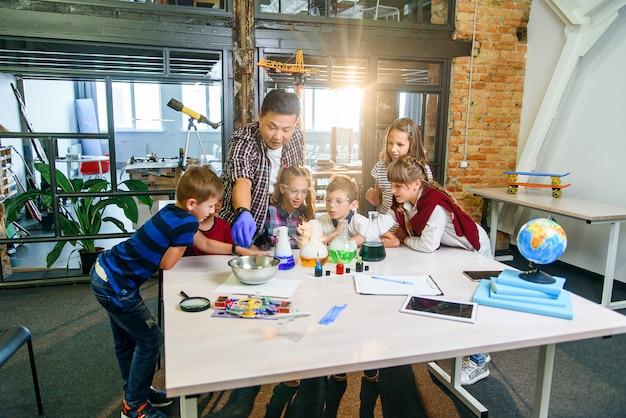 Uczniowie z młodym nauczycielem na lekcji chemii wykonujący ciekawe eksperymenty z wykorzystaniem płynów chemicznych i suchego lodu we współczesnej klasie laboratoryjnej.